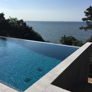 Example of a large minimalist backyard stone and rectangular aboveground hot tub design in New York
