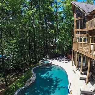 Diseño de piscina con fuente rústica, grande, tipo riñón, en patio trasero, con adoquines de piedra natural