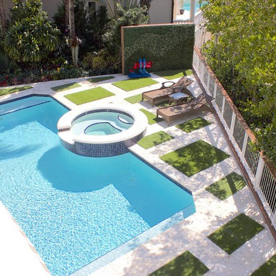 Mid-sized island style backyard concrete paver and rectangular hot tub photo in Miami