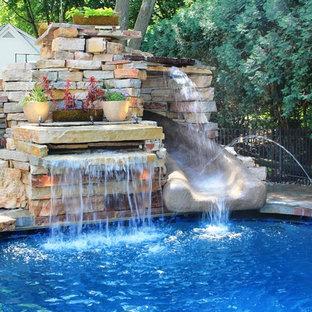 Imagen de piscina con tobogán natural, bohemia, de tamaño medio, a medida, en patio trasero, con adoquines de hormigón