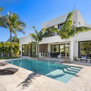 На фото: прямоугольный бассейн на заднем дворе в современном стиле с покрытием из плитки с