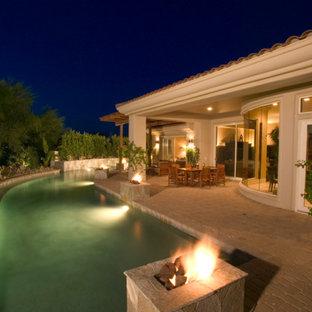 Modelo de piscina con fuente alargada, tradicional renovada, grande, en forma de L, en patio trasero, con adoquines de ladrillo