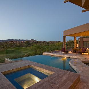 Ejemplo de piscina con fuente infinita, actual, de tamaño medio, a medida, en patio trasero, con adoquines de piedra natural