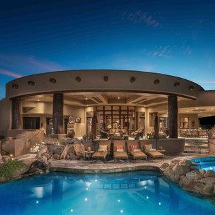 Modelo de piscinas y jacuzzis de estilo americano, grandes, a medida, en patio trasero, con adoquines de piedra natural