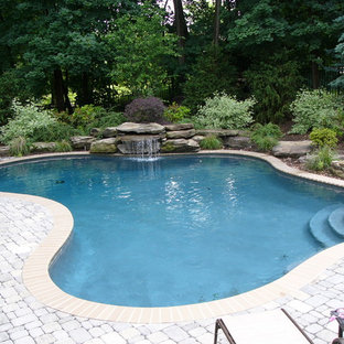 Pool fountain - mid-sized transitional backyard brick and custom-shaped natural pool fountain idea in New York