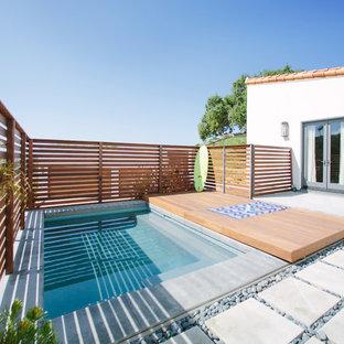 Modelo de piscina actual, rectangular, en patio trasero, con adoquines de hormigón