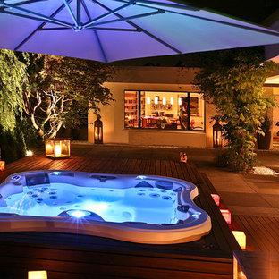 Diseño de piscinas y jacuzzis elevados, contemporáneos, a medida, en patio trasero, con entablado