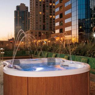 Foto de piscinas y jacuzzis elevados, contemporáneos, grandes, a medida, en patio trasero, con granito descompuesto