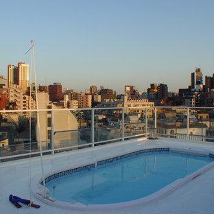 Imagen de piscinas y jacuzzis elevados, actuales, grandes, redondeados, en azotea, con losas de hormigón