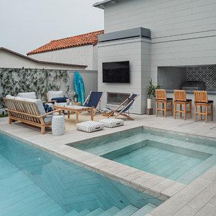 Immagine di una piscina stile marino rettangolare con una vasca idromassaggio e piastrelle