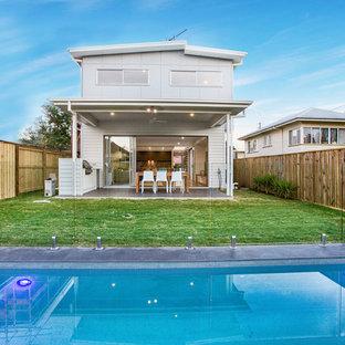 Foto de piscina alargada, nórdica, rectangular, en patio trasero, con adoquines de hormigón
