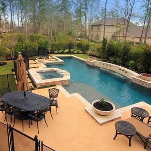 Imagen de piscina alargada, clásica, grande, rectangular, en patio trasero, con adoquines de piedra natural