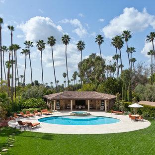 Immagine di un'ampia piscina mediterranea rotonda dietro casa con piastrelle e una dépendance a bordo piscina