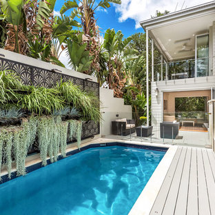 Photo of a tropical side yard rectangular lap pool in Brisbane with decking.