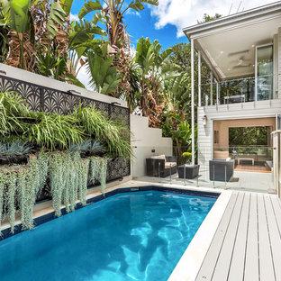 Esempio di una piscina monocorsia tropicale rettangolare nel cortile laterale con pedane