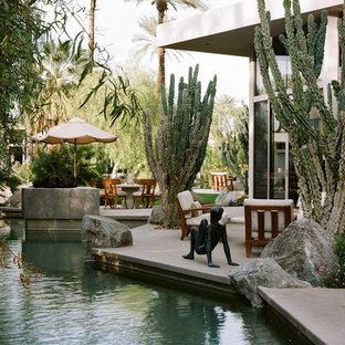 Ejemplo de piscina alargada, de estilo zen, de tamaño medio, a medida, en patio trasero, con losas de hormigón