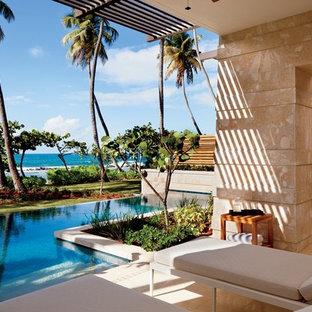 Ejemplo de piscina infinita, tropical, a medida, en patio trasero, con suelo de baldosas