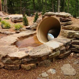 Imagen de piscina con tobogán natural, rural, grande, a medida, en patio trasero, con suelo de hormigón estampado
