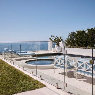 Ispirazione per una grande piscina monocorsia stile marino rettangolare dietro casa con una vasca idromassaggio