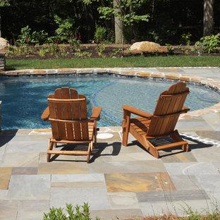 Ejemplo de piscinas y jacuzzis alargados, tradicionales, grandes, tipo riñón, en patio trasero, con suelo de baldosas