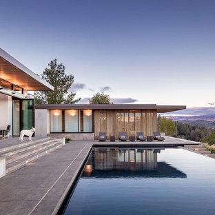 Foto de piscina infinita, contemporánea, rectangular, en patio trasero, con adoquines de hormigón