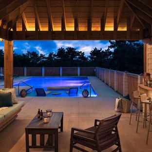 Ejemplo de piscina costera, grande, rectangular, en patio lateral, con losas de hormigón
