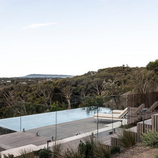 Design ideas for a large beach style backyard rectangular infinity pool in Melbourne with decking.
