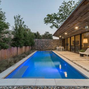 Foto di una piccola piscina monocorsia industriale rettangolare dietro casa con lastre di cemento e fontane