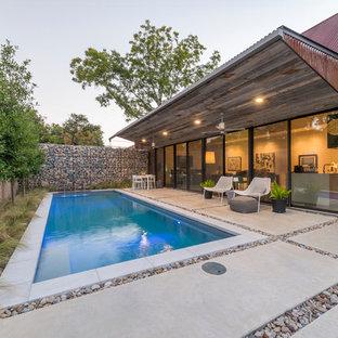 Modelo de piscina con fuente alargada, industrial, pequeña, rectangular, en patio trasero, con adoquines de hormigón