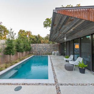 Kleines Industrial Sportbecken hinter dem Haus in rechteckiger Form mit Wasserspiel und Betonplatten in Dallas