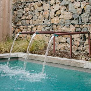 Esempio di una piccola piscina monocorsia industriale rettangolare dietro casa con fontane e lastre di cemento