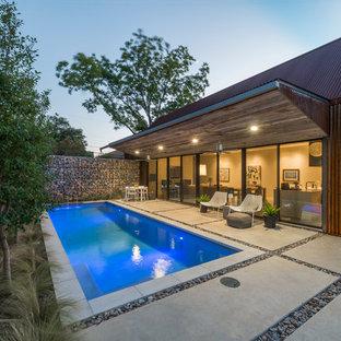 Esempio di una piccola piscina monocorsia industriale rettangolare dietro casa con lastre di cemento e fontane
