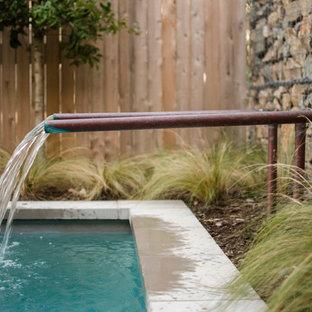 Idee per una piccola piscina monocorsia industriale rettangolare dietro casa con fontane e lastre di cemento