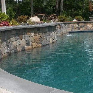 Huge mountain style backyard stone and custom-shaped natural hot tub photo in Boston