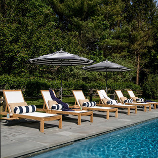 This is an example of an expansive beach style backyard custom-shaped natural pool in New York with natural stone pavers.