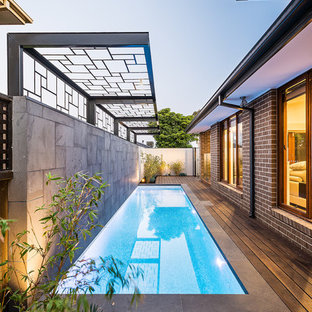 Inspiration for a small contemporary side yard rectangular lap pool in Melbourne with decking.