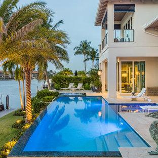 Foto de piscinas y jacuzzis infinitos, mediterráneos, rectangulares, en patio trasero, con suelo de baldosas