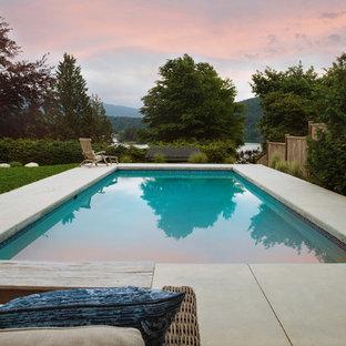 Imagen de piscina moderna, de tamaño medio, rectangular, en patio trasero, con losas de hormigón