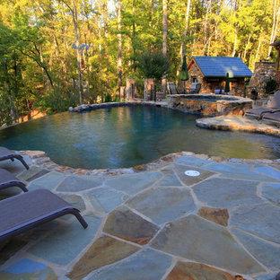 Esempio di una grande piscina a sfioro infinito rustica personalizzata dietro casa con una dépendance a bordo piscina e pavimentazioni in pietra naturale