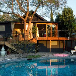 Imagen de piscina vintage, redondeada, en patio trasero, con adoquines de piedra natural