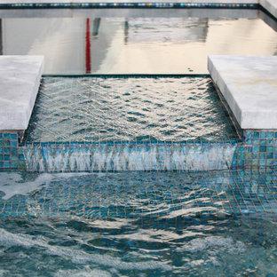 Imagen de piscina con fuente alargada, minimalista, grande, en forma de L, en patio trasero, con losas de hormigón