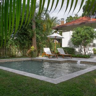 Modelo de piscinas y jacuzzis naturales, minimalistas, pequeños, en forma de L, en patio trasero, con adoquines de piedra natural