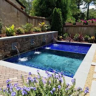 Modelo de piscina con fuente contemporánea, de tamaño medio, rectangular, en patio trasero, con adoquines de ladrillo