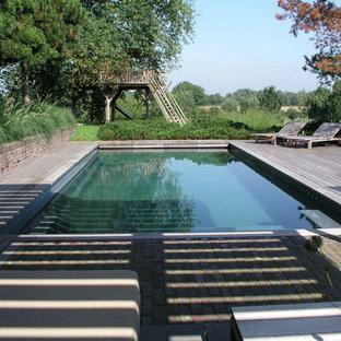 Foto de piscina alargada, campestre, grande, rectangular, con entablado