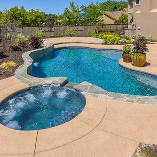 Foto de piscinas y jacuzzis exóticos, grandes, tipo riñón, en patio trasero, con adoquines de piedra natural