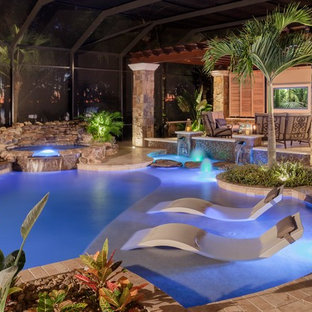 Mid-sized mountain style backyard stone and custom-shaped pool fountain photo in Tampa