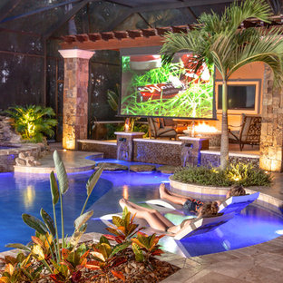Example of a mid-sized mountain style backyard stone and custom-shaped pool fountain design in Tampa