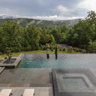Diseño de piscinas y jacuzzis infinitos, contemporáneos, grandes, rectangulares, en patio trasero, con losas de hormigón