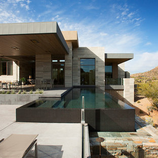 Inspiration for a huge modern side yard stone and rectangular infinity pool remodel in Phoenix