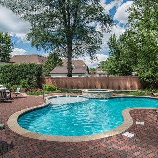 Idee per una piscina chic personalizzata di medie dimensioni e dietro casa con una vasca idromassaggio e pavimentazioni in mattoni